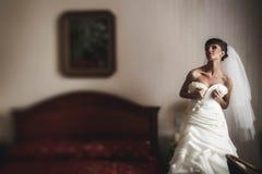 La jeune mariée dans la robe de mariage pose sur le lit de fond Photos stock