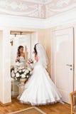 La jeune mariée dans la robe de mariage regarde dans le miroir Image stock