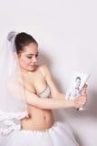 La jeune mariée dans le voile et la jupe cassent la photo de marié, fond gris Images stock
