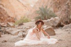 La jeune mariée dans la longs robe et chapeau s'assied en canyon en sable Photographie stock libre de droits