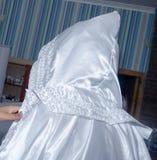 La jeune mariée dans un manteau blanc avec un capot, est de retour Image stock