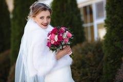 La jeune mariée dans un manteau chaud et chaud pose dehors dans la perspective des arbres grands La fille sourit et respire Photo stock