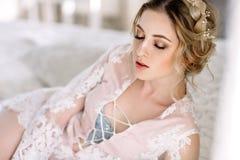 La jeune mariée dans un peignoir à la fenêtre de chambre à coucher pendant le matin images libres de droits