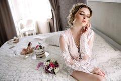 La jeune mariée dans un peignoir à la fenêtre de chambre à coucher pendant le matin photos libres de droits