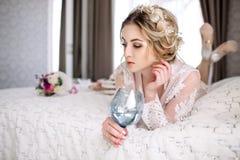 La jeune mariée dans un peignoir à la fenêtre de chambre à coucher pendant le matin image stock
