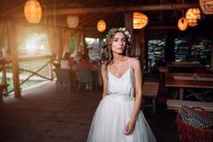 La jeune mariée dans une robe blanche et une guirlande des fleurs est dans la recherche Photographie stock