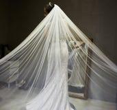 La jeune mariée dans une robe de style de la sirène blanche avec le voile a étendu photographie stock
