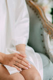La jeune mariée dans une robe longue s'assied sur le lit avec ses mains étreintes, sur le doigt de la jeune mariée l'anneau de ma Photos libres de droits