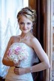 La jeune mariée de beauté dans la robe de mariée avec le bouquet et la dentelle voilent à l'intérieur Photographie stock libre de droits