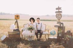 La jeune mariée de sourire avec le bouquet et le marié heureux dans le costume de vintage s'asseyent sur le sofa démodé entouré p Photographie stock libre de droits
