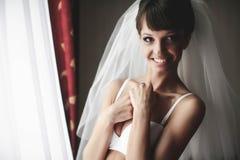 La jeune mariée de sourire pose dans la blancheur sur les rideaux en fond images libres de droits