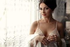 La jeune mariée de tendresse tient la fenêtre proche Photo stock