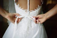 La jeune mariée elle-même attache une robe de mariage d'arc photo libre de droits