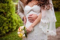 La jeune mariée embrasse la jeune mariée photographie stock