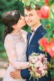 La jeune mariée embrasse le marié de sourire dans la joue tout en tenant le bouquet l'épousant Images stock