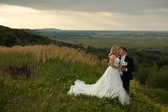 La jeune mariée embrasse le visage du marié tendrement tandis qu'ils se tiennent sur un h vert photo libre de droits