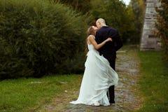 La jeune mariée embrasse un fiancé tandis que sa robe couvre ses jambes image stock