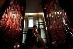 La jeune mariée embrasse un marié se tenant avec lui dans les lumières des lampes Images libres de droits