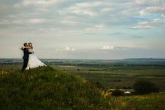 La jeune mariée embrasse un marié se tenant sur une colline avec une grande vue sur photo stock