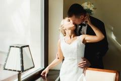 La jeune mariée embrasse un marié tandis qu'il l'étreint par derrière la position dans t Images stock