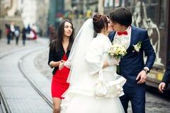 La jeune mariée embrasse un marié tout en marchant avec des amis autour de la ville Image stock