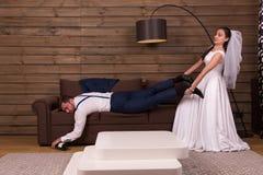 La jeune mariée essaye de réveiller un marié de sommeil ivre Photographie stock