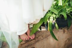 La jeune mariée est aux pieds nus avec les pieds nus se tenant sur une étape près de l'eau Photographie stock libre de droits