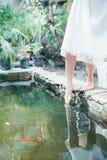 La jeune mariée est aux pieds nus avec les pieds nus se tenant sur une étape près de l'eau Image stock