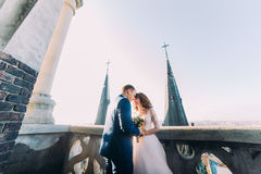 La jeune mariée et le fiancé ont le moment sensuel sur le balcon de la cathédrale gothique antique Images libres de droits