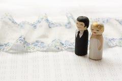 La jeune mariée et le groome durcissent les chiffres en bois épatants de griffonnage sur le fabr blanc Image libre de droits