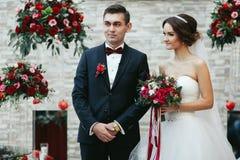 La jeune mariée et le jeune marié se tiennent souriants pendant le ceremon d'engagement Photographie stock libre de droits