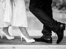 La jeune mariée et le marié nuptiale se tiennent sur le banc photo stock