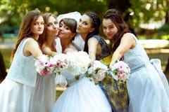 La jeune mariée et les demoiselles d'honneur atteignent des mains avec des bouquets au cameraman images stock