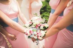 La jeune mariée et les demoiselles d'honneur montrent de belles fleurs sur leurs mains Photos libres de droits