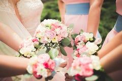 La jeune mariée et les demoiselles d'honneur montrent de belles fleurs sur leurs mains Images stock