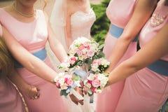 La jeune mariée et les demoiselles d'honneur montrent de belles fleurs sur leurs mains Photo libre de droits