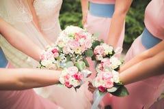 La jeune mariée et les demoiselles d'honneur montrent de belles fleurs sur leurs mains Photographie stock