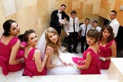 La jeune mariée et les demoiselles d'honneur s'asseyent sur les escaliers blancs tandis que marié et le GR Photo stock