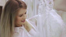 La jeune mariée féminine d'aides de consultant en matière de boutique choisit la robe à la boutique de la mode de mariage Foyer s banque de vidéos