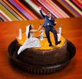 La jeune mariée fait la proposition au marié sur le grand gâteau photographie stock libre de droits