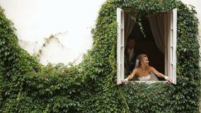 La jeune mariée gaie ouvre la fenêtre tandis que le marié l'embrasse La maison est couverte de belles herbes banque de vidéos