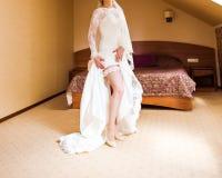 La jeune mariée habille la jarretière sur la jambe Photo stock