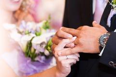 La jeune mariée habille un anneau de mariage au marié Photos stock