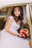 La jeune mariée heureuse de nouveaux mariés s'assied sur une banquette arrière de voiture de vintage Image stock