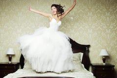La jeune mariée heureuse sautent sur le lit. Image libre de droits