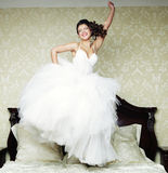 La jeune mariée heureuse sautent sur le lit. Image stock