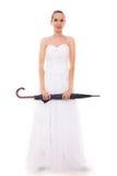 La jeune mariée intégrale dans la robe de mariage tient le parapluie Images stock