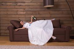 La jeune mariée ivre avec la bouteille d'alcool détendent sur le divan Photographie stock