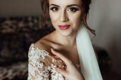 La jeune mariée magnifique avec le maquillage de mode et la coiffure dans un luxe les épousent photos stock