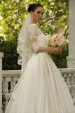La jeune mariée magnifique avec les cheveux foncés porte la robe élégante de mariage photographie stock